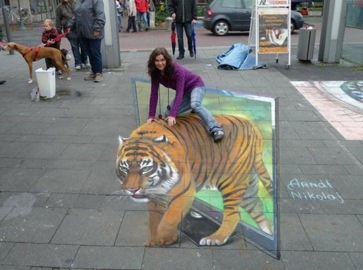 chica montando tigre pintado en la vereda