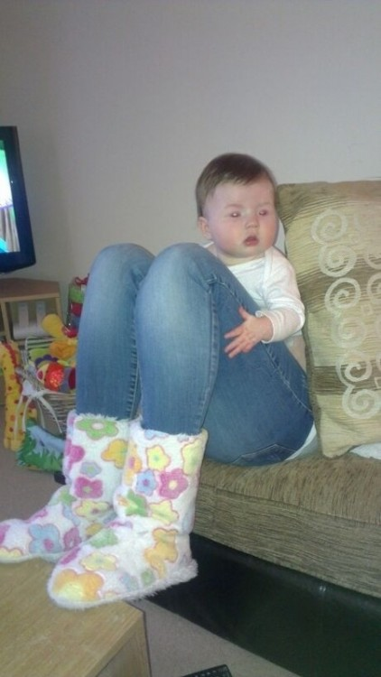 Una bebé sentada en un sillón donde parece tener piernas de mujer