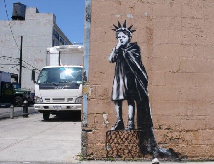 Grafiti de Bansky simulando a la estatua de la libertad