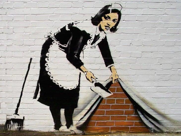 Grafiti de Bansky que muestra una mujer levantando una cortina y echando basura dentro