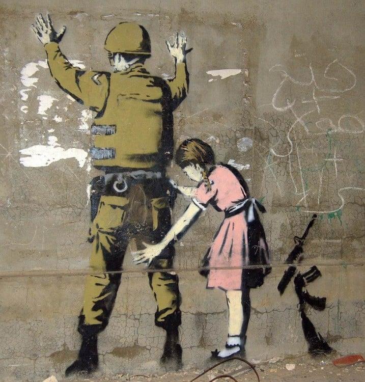 Obra urbana de Bansky donde una niña revisando a un soldado