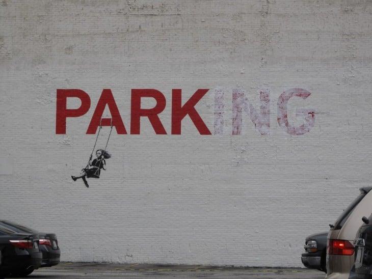 Arte urbana por Bansky de una niña columpiándose en la palabra Parking