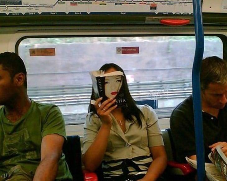 Mujer sentada en el transporte público con la portada de un libro frente a su cara