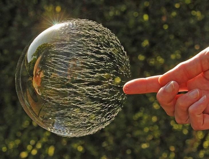 una mano reventando una burbuja