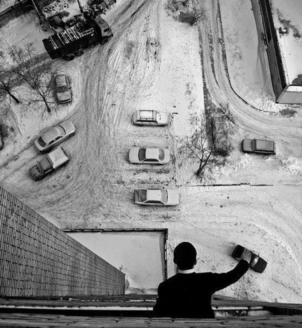 una persona desde un edificio simulando que juega a los carritos