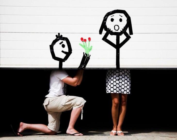 dos personas detrás de un portón que simulan la escena de pedir matrimonio