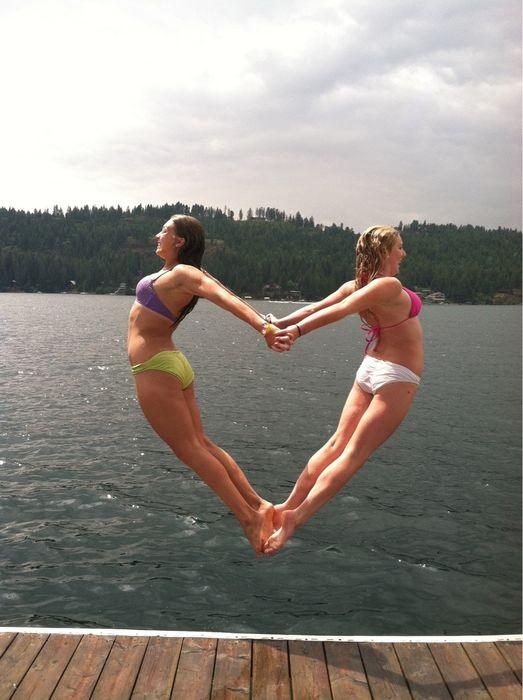 Dos chicas tomadas de las manos formando un corazón a punto de aventarse al agua