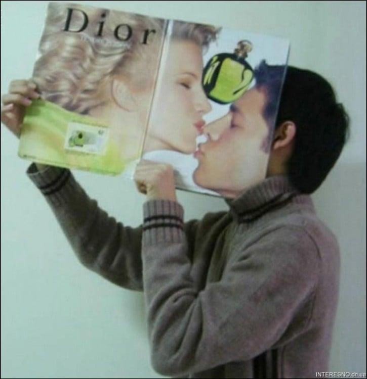 un chico con una revista frente a su cara que parece estar besando a una modelo de revista