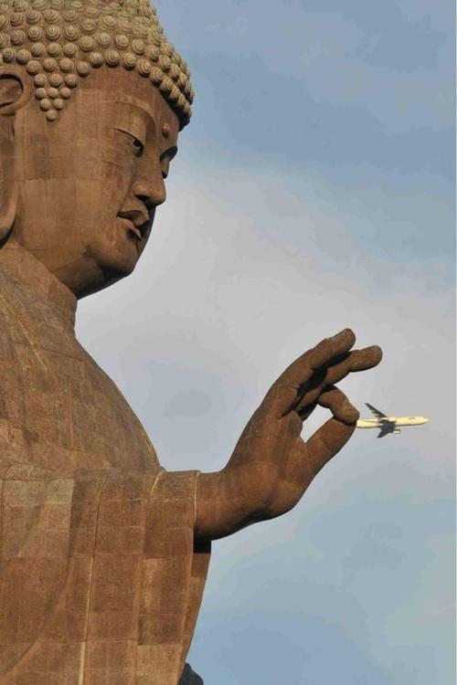 Estatua de un buda que parece sostener un avión en la mano