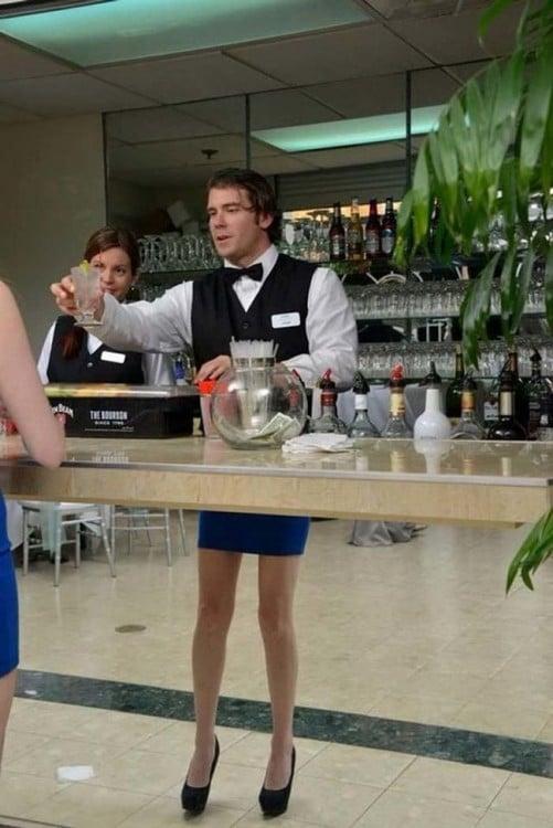 Mesero detrás de una barra donde en la parte delantera simula tener falda y piernas de mujer