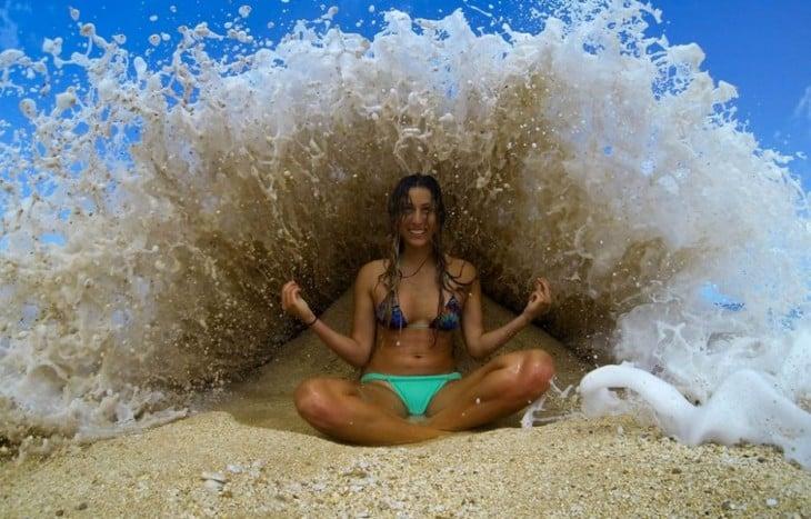 una chica sentada en la playa mientras una ola de agua pasa por encima de ella