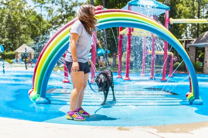 una chica mojándose con su mascota debajo de un puente de colores