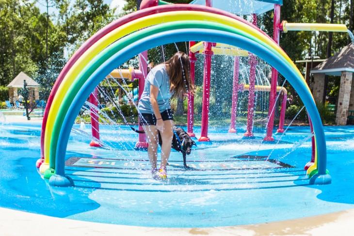 una chica pasando debajo de un puentesito de colores con agua