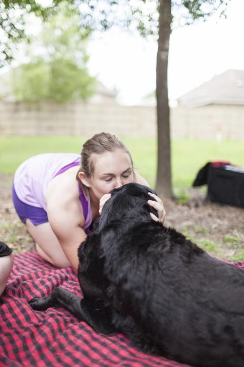 una chica dando un beso a perro acostado en el suelo