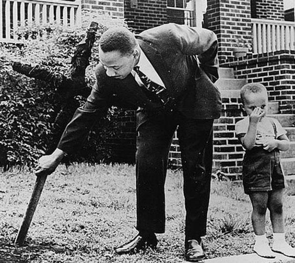 Martin Luther King, con su hijo, removiendo una cruz quemada en su jardin, 1960