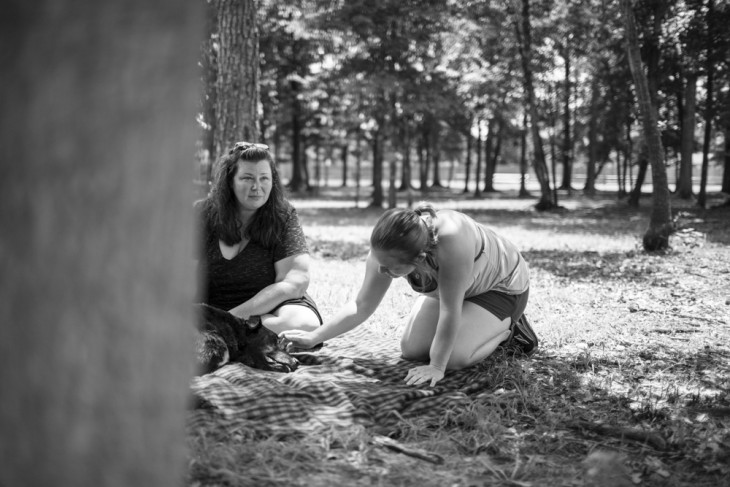 fotografía de dos mujeres cerca de un perro acostado en el suelo de un parque