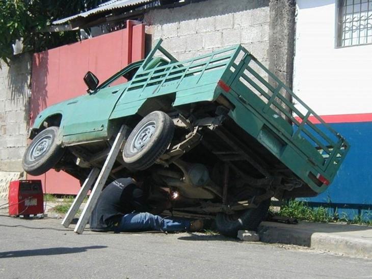 HOMBRE TRATANDO DE ARREGLAR UN CARRO