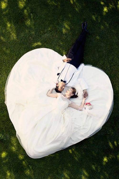 novios acostados y un vestido en forma de corazon