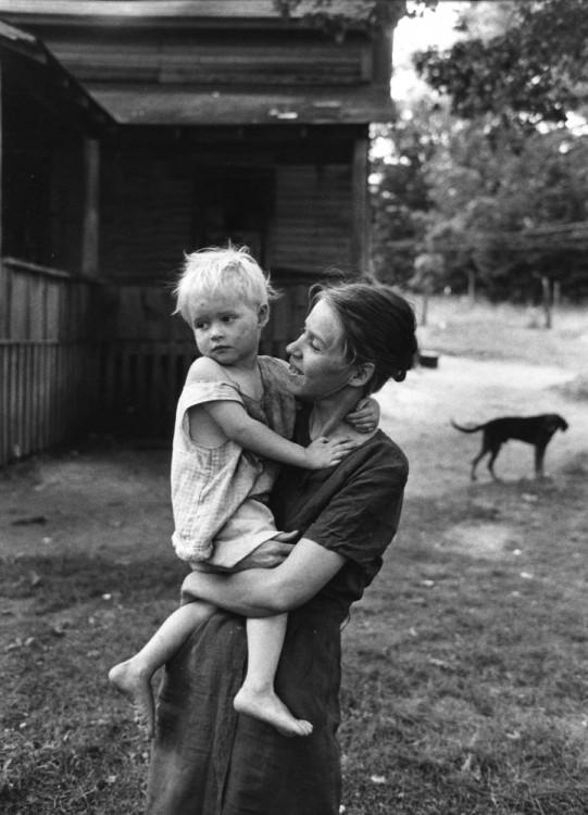 mujer cargando a su hijo en el patio de su casa