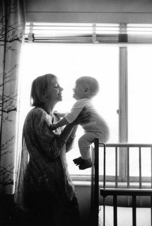 una mujer frente a su hijo sentado en una cuna sonriendo