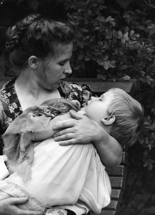 una mujer durmiendo a su hijo en sus brazos