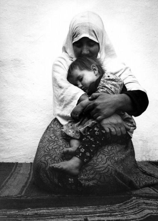 Mujer sentada en el suelo abrazando a su hijo mientras duerme