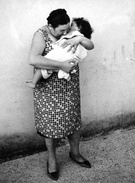 una mujer parada en la calle con su hijo en su brazos