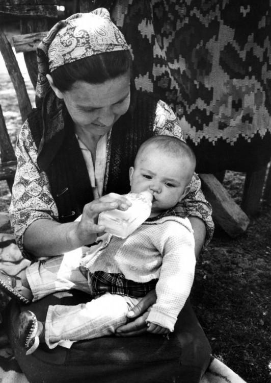Fotografía de una mujer alimentando a un bebé en sus piernas