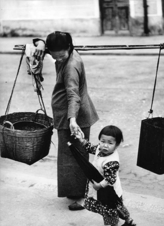 Mujer china cargando unas canastas y con un niño de la mano