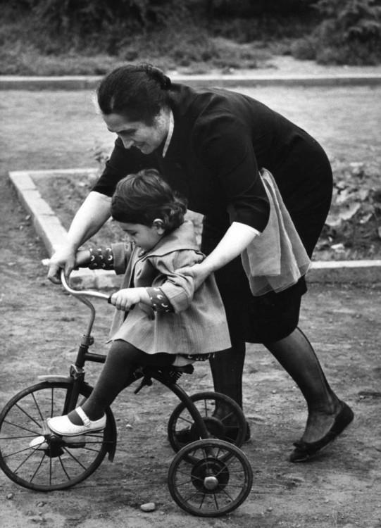 una mujer enseñando a su niño a andar en bici