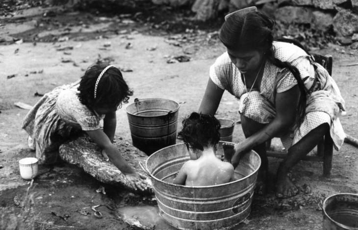 mujer bañando a su hijo dentro de una tina al aire libre