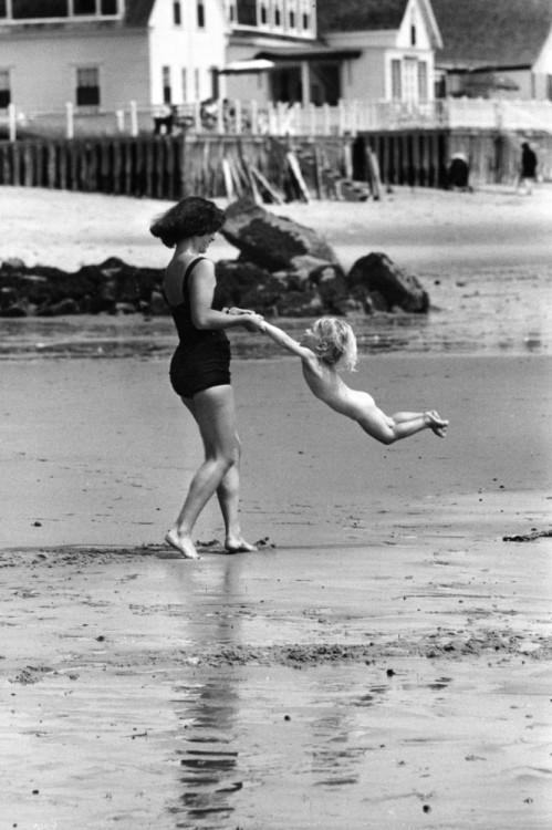 mujer cargando a un niño de las manos