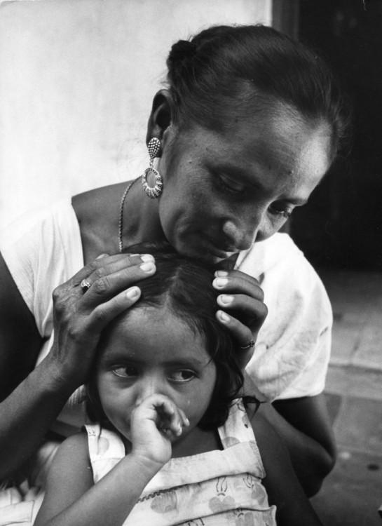 Mujer con sus manos en la cabeza de su hija