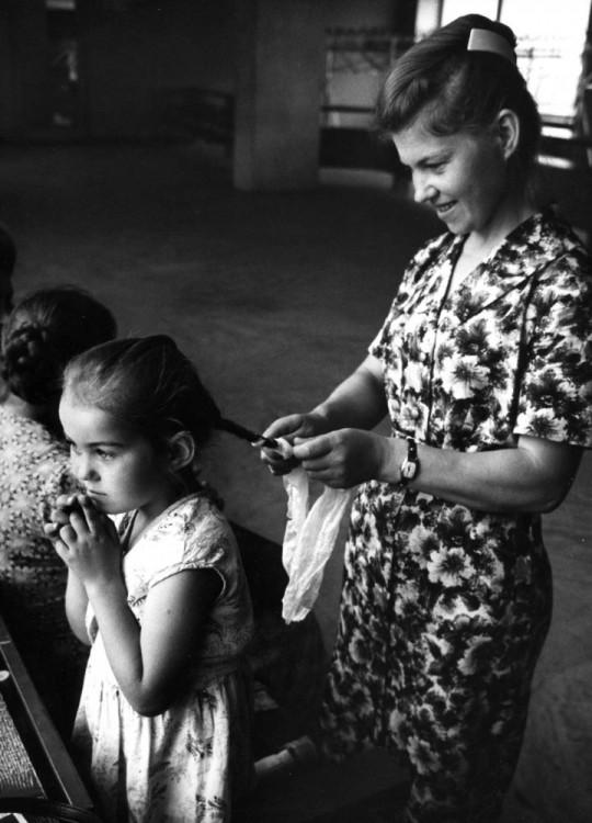 madre haciendo una trenza en el cabello de su hija