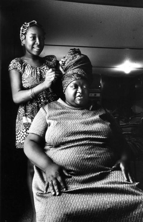 una chica envolviendo el cabello de su madre sentada frente a ella