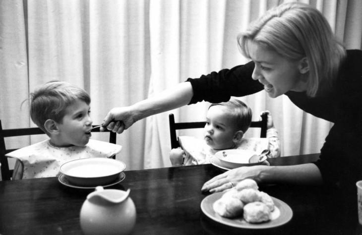 mujer alimentando a sus dos hijos en la mesa