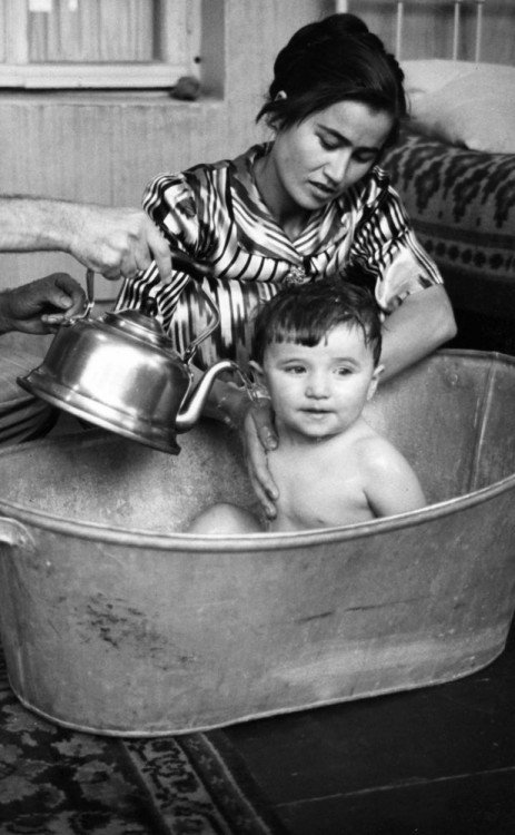 una madre bañando a su hijo dentro de una tina de aluminio
