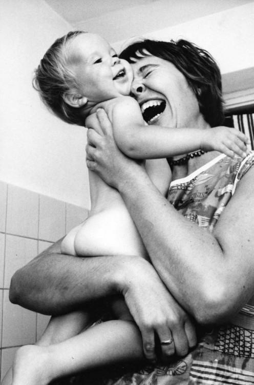 Fotografía de una madre abrazando y riendo con su bebé