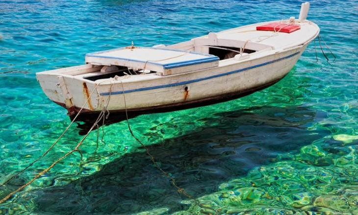 bote flotando sobre el agua clara de Primosten en Croacia