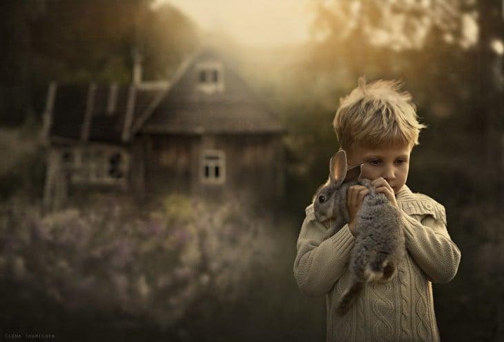 niño con su conejo en frente de la casa