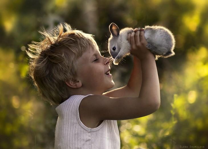 niño alegre sujetando a su conejo