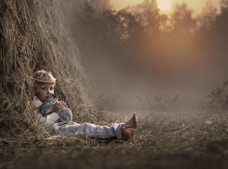 niño sentado al lado de un árbol con un conejo