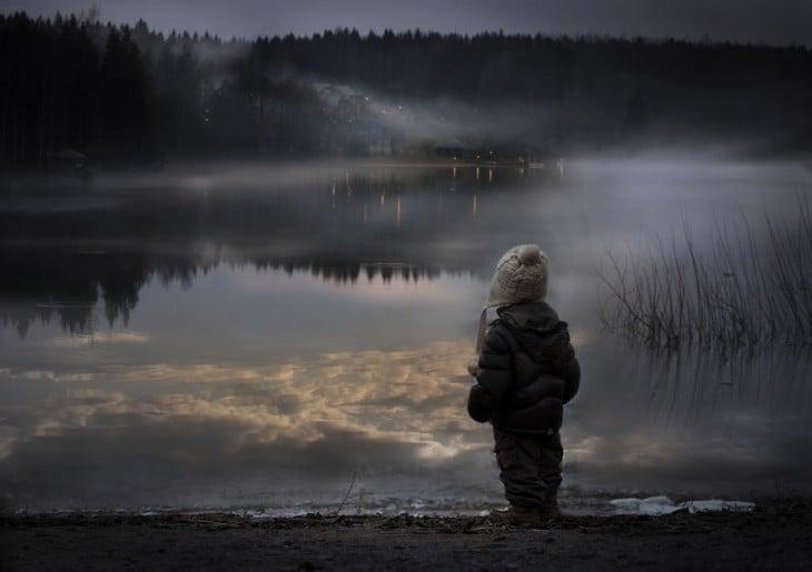 niño viendo el atardecer en un lago