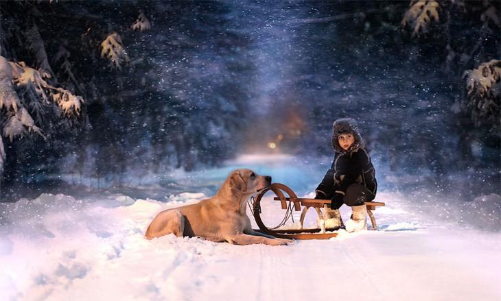 niño con su perro sentado en el trineo