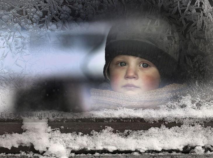 niño en la ventana con nieve