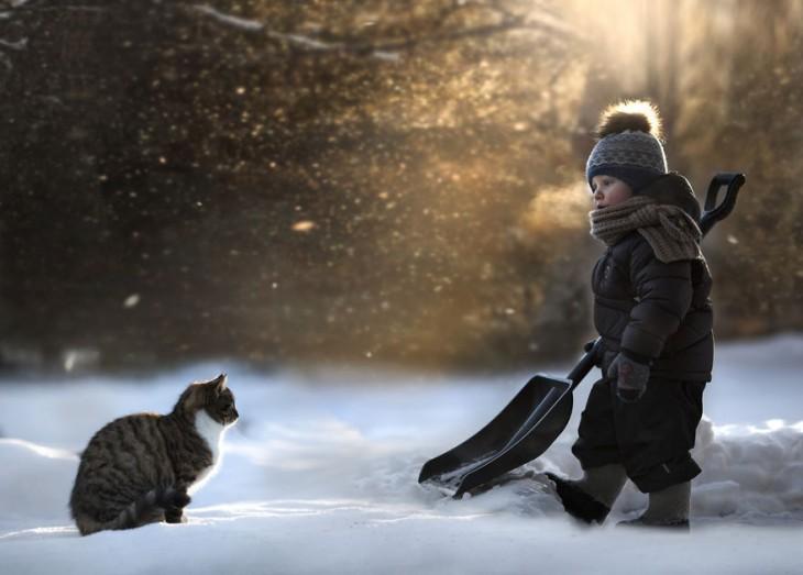 niño con una pala juntando nieve al lado del gato