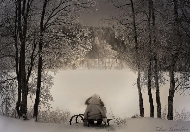 niño sentado en su trineo viendo la casa