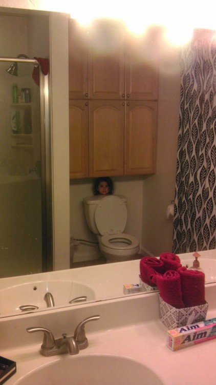 niña escondida detrás del deposito de un inodoro