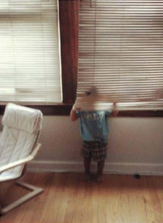 Niño escondido detrás de una persiana