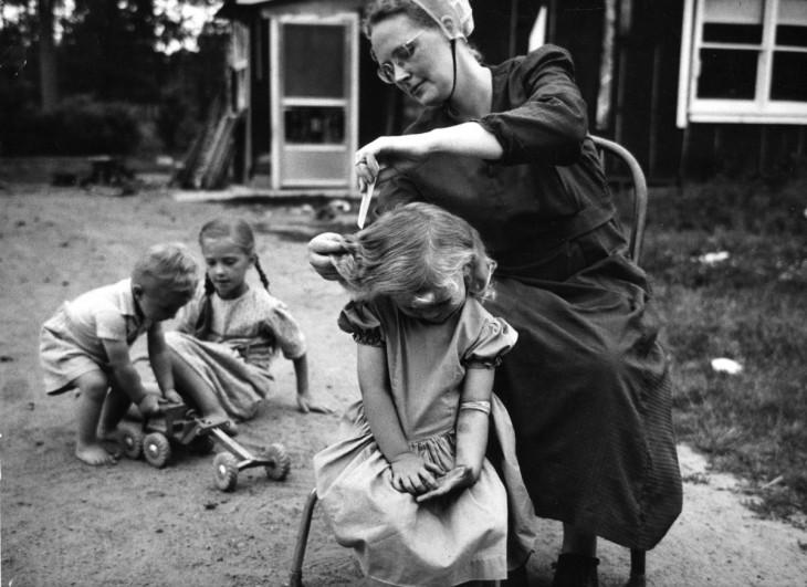 madre peinando a sus tres hijas